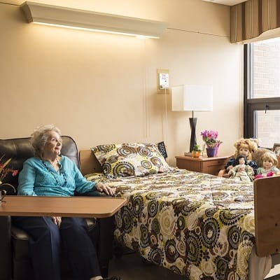 Memory care resident relaxing in her spacious private room