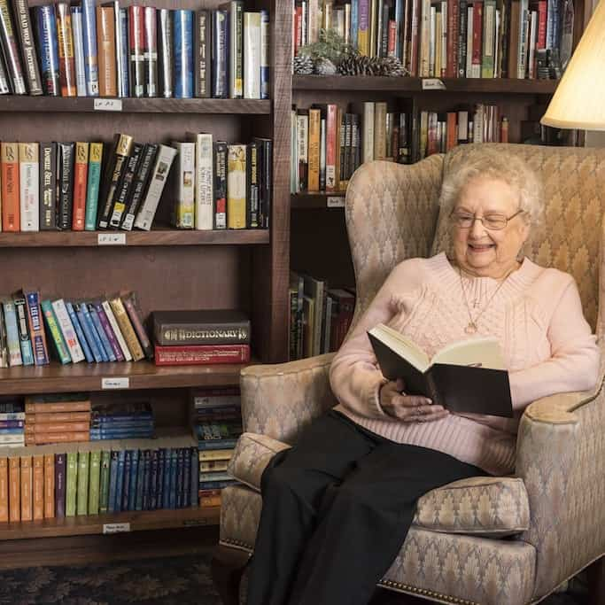 Resident reading a book in library
